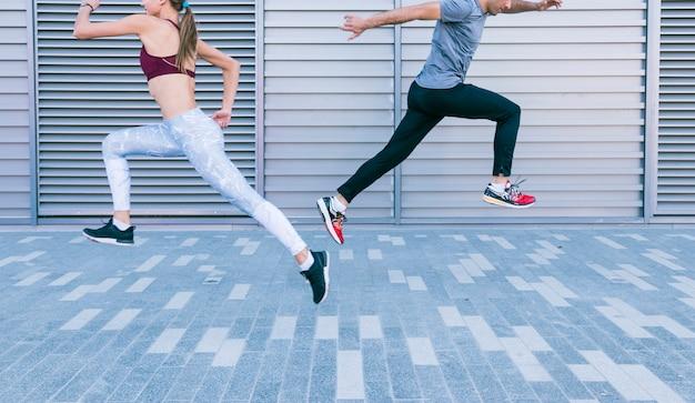 Pareja deportiva pareja corriendo y saltando en el aire