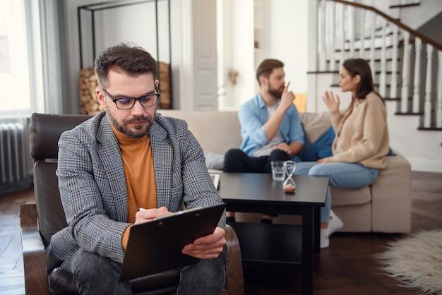 La pareja deprimida está sentada en el sofá y discutiendo mientras el psicólogo está tomando notas.