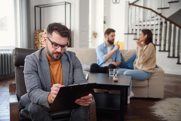 La pareja deprimida está sentada en el sofá y discutiendo entre sí mientras el médico psicólogo está tomando notas.