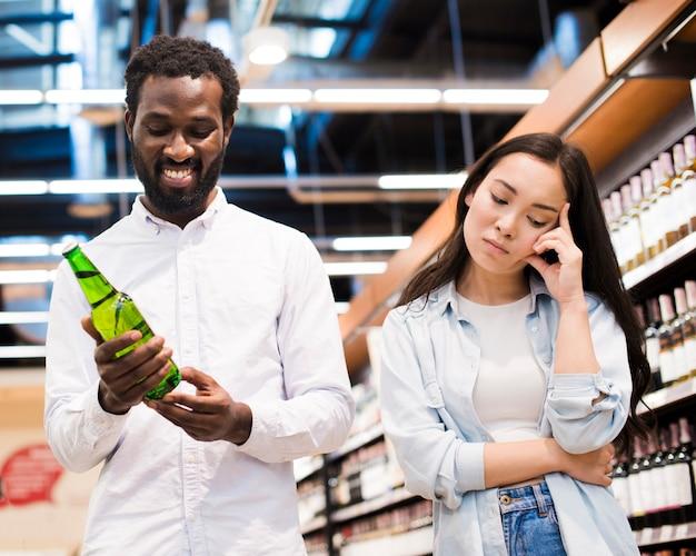 Pareja en desacuerdo sobre la cerveza en la tienda de comestibles