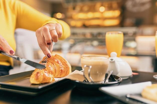 Pareja desayunando en la cafetería, ella está comiendo un croissant, ambos están tomando un zumo de naranja.