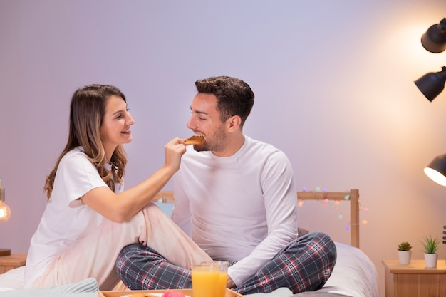 Pareja desayunando en la cama
