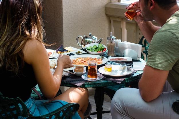 Pareja desayunando en la terraza del café