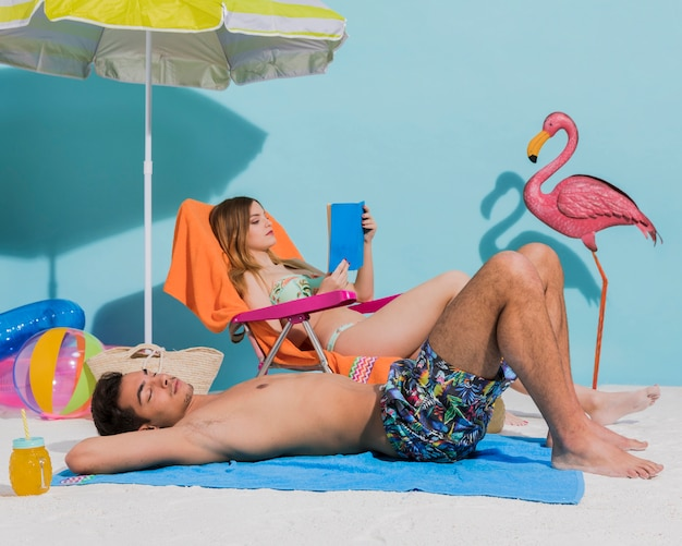 Pareja descansando en la playa juntos