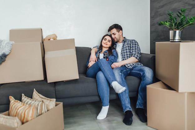 Pareja descansando en el sofá después de mudarse, el hombre y la mujer descansando en el sofá se acaban de mudar al apartamento con cajas de cartón en el piso