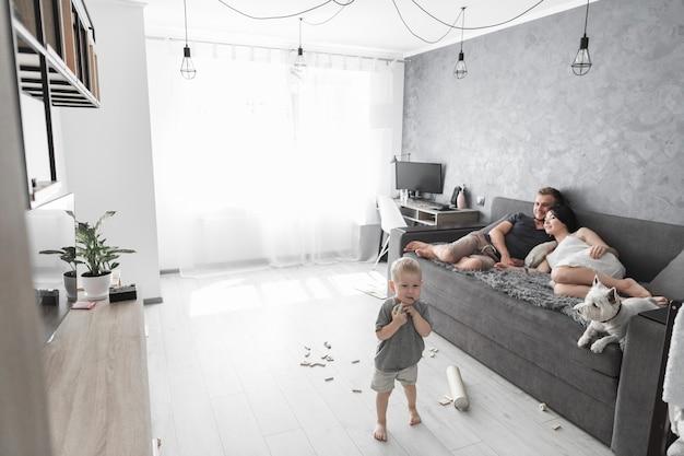Pareja descansando en el sofá con un perro y su hijo jugando con juguetes en casa