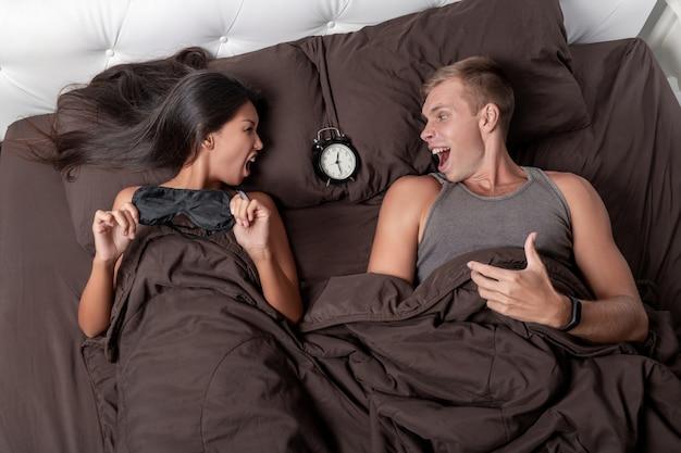 La pareja con descontento y odio está tratando de dormir, pero el despertador no les permite hacerlo.