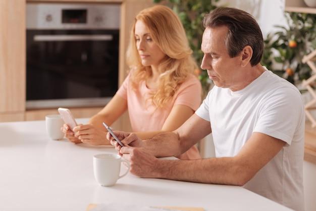 Pareja descuidada moderna obsesionada sentada en casa y usando teléfonos inteligentes sin prestar atención el uno al otro