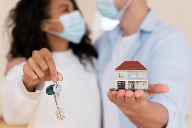 Pareja desenfocada con máscaras médicas sosteniendo nuevas llaves de casa y casa en miniatura