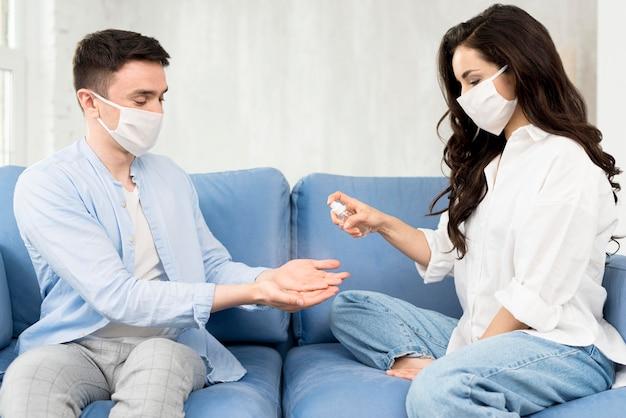 Pareja desinfectando las manos en casa