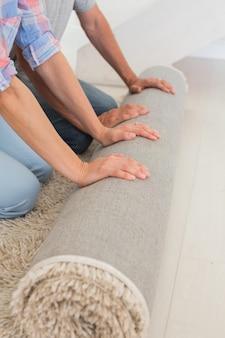 Pareja desplegando una nueva alfombra