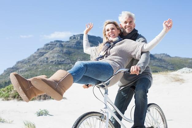 Pareja despreocupada yendo en bicicleta en la playa