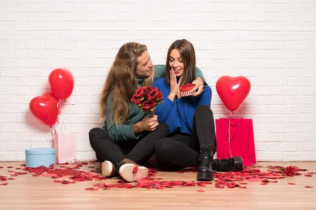 Pareja en el día de san valentín con flores y regalos