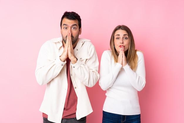 Pareja en el día de san valentín sobre pared rosa aislado mantiene la palma de la mano la persona pide algo