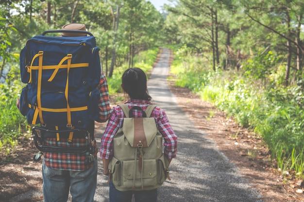 Pareja en un día de trekking en bosque tropical junto con mochilas en el bosque, aventura, viajes, turismo, caminata.
