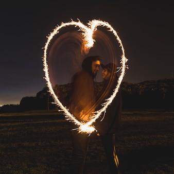 Pareja dibujando corazón de bengalas en calle oscura