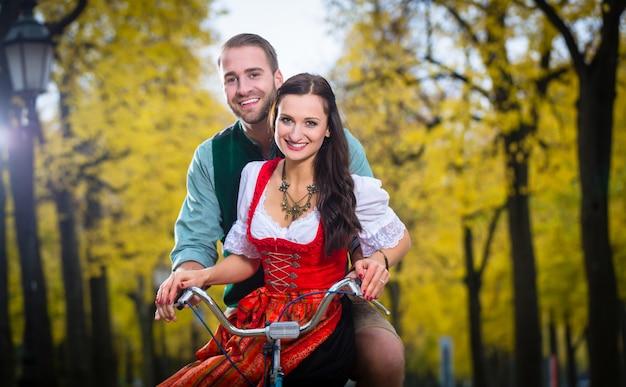 Pareja en dirndl y pantalones de cuero juntos en una bicicleta.