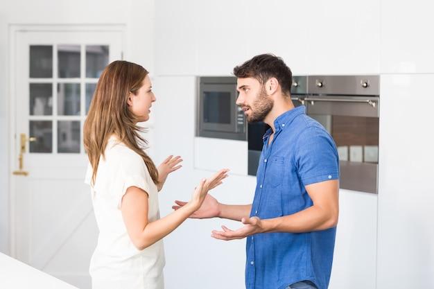 Pareja discutiendo mientras está parado en la cocina