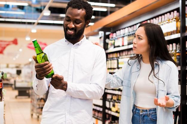 Pareja discutiendo sobre la cerveza en la tienda de comestibles