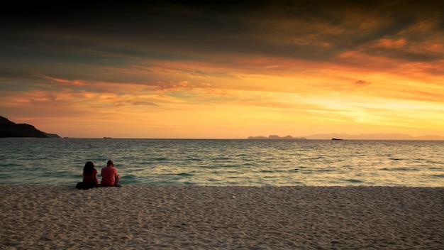 Pareja disfruta del amanecer paisaje marino en lipe