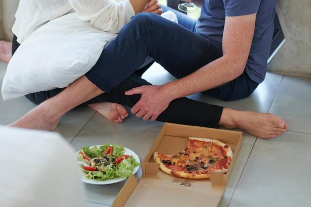 Pareja disfrutando de una cena de pizza y ensalada