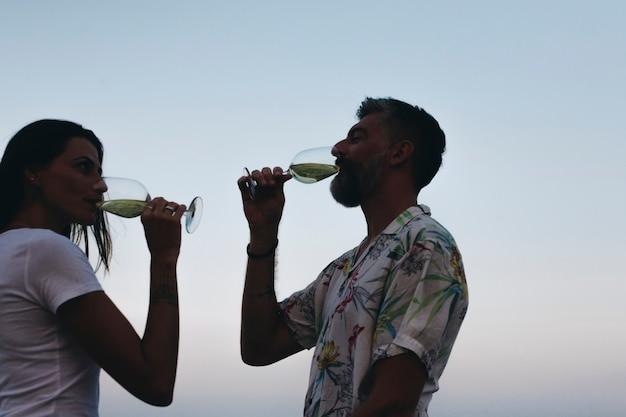 Pareja disfrutando de una copa de vino en la playa