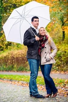 Pareja disfrutando día de otoño paseando a pesar de la lluvia.