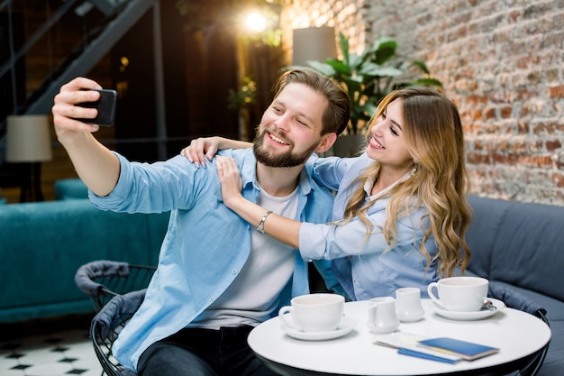 Pareja disfrutando el tiempo juntos, haciendo selfie, sentado en la mesa de café y tomando café.