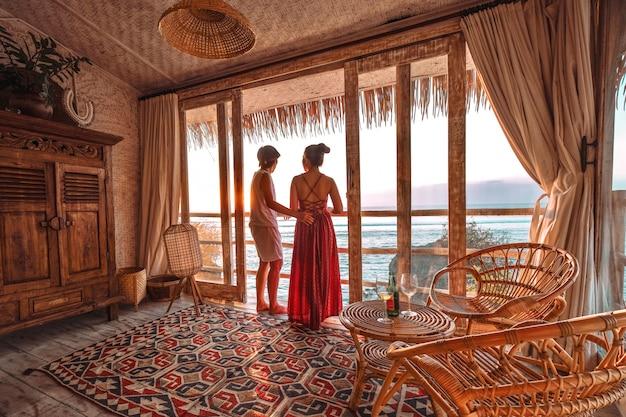 Pareja disfrutando de las vacaciones de la mañana en un bungalow de playa tropical con vista al mar vacaciones relajantes en uluwatu bali, indonesia