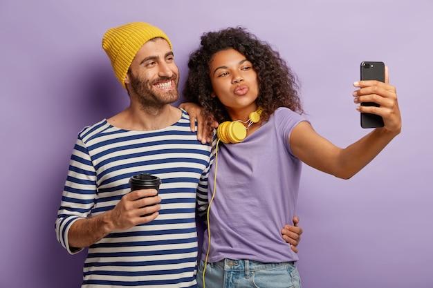 Pareja diversa positiva posa para hacer selfie, sonreír y hacer muecas del dispositivo, beber café para llevar, usar ropa informal, abrazarse contra la pared púrpura tecnología, estilo de vida