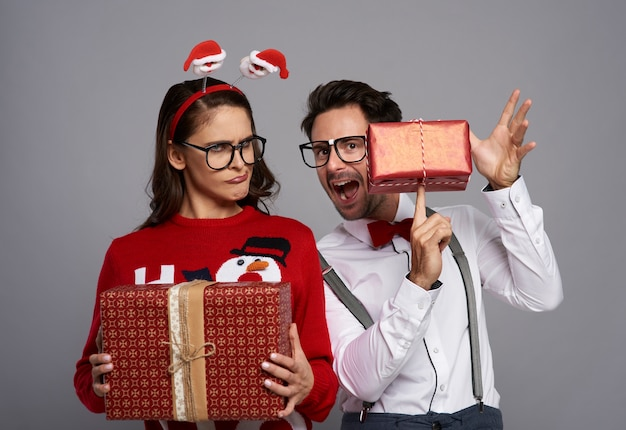 Pareja divertida con muchos regalos de navidad