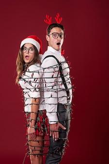 Pareja divertida nerd se enredan en luces de navidad