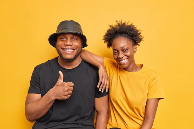 La pareja se divierte muestra una excelente sonrisa de signo felizmente vestida con ropa casual aislada en amarillo vivo