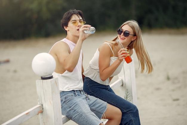 Pareja diviértete en una playa con bebidas