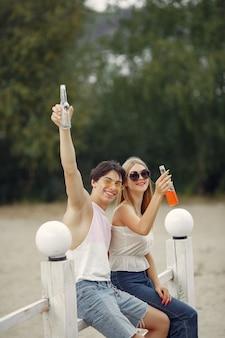 Pareja divirtiéndose en una playa con bebidas