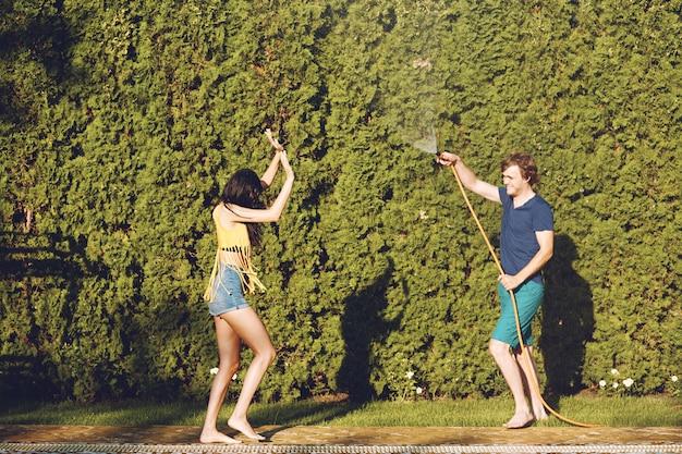 Pareja divirtiéndose se vierte con manguera de jardín