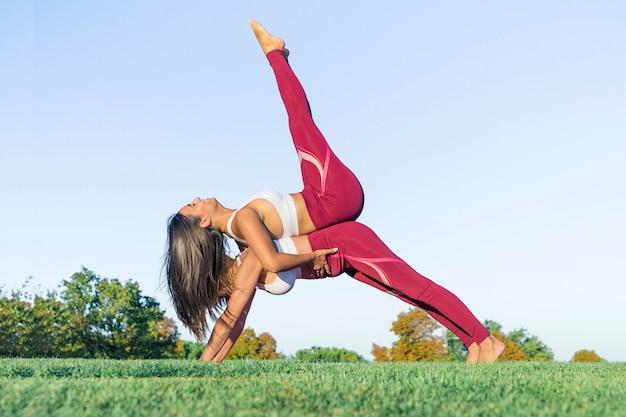 Pareja de dos mujeres, una joven y otra mayor, realizan ejercicios de estiramiento y yoga con figuras acrobáticas al aire libre vestidas con ropa deportiva.