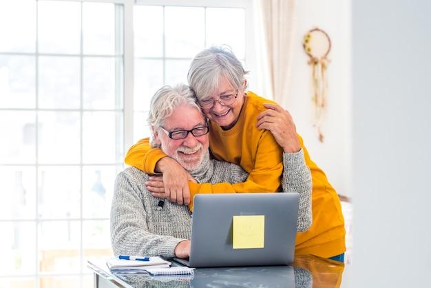Pareja de dos personas mayores felices trabajando y usando la computadora portátil juntos en casa sonriendo y divirtiéndose juntos - estilo de vida de bloqueo