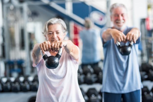 Pareja de dos personas mayores o jubilados activos y saludables o personas maduras haciendo ejercicio juntos en el gimnasio sosteniendo una pesa en sus manos y haciendo sentadillas - concepto de dieta de estilo de vida fitness