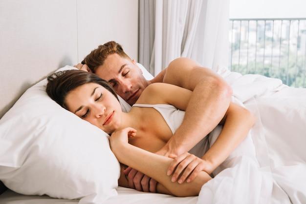 Pareja durmiendo y abrazándose en la cama