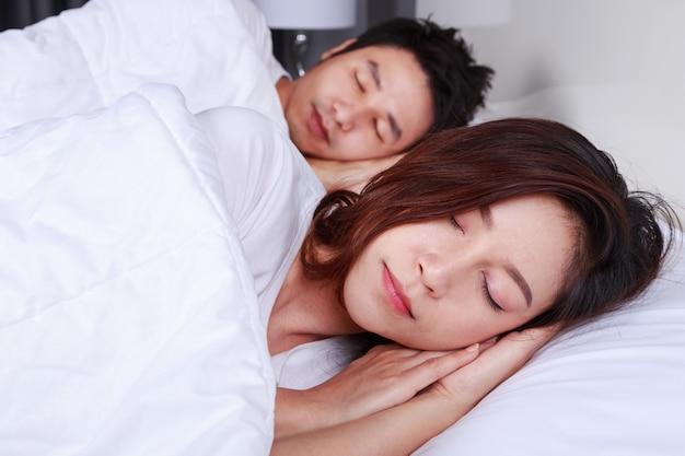 Pareja durmiendo en una cama cómoda en el dormitorio en casa