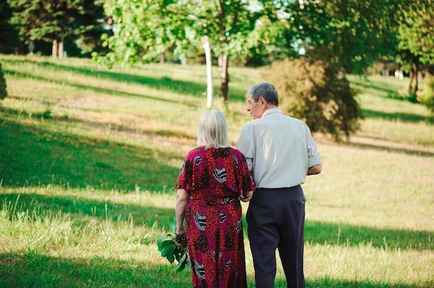 Pareja de edad en el amor cogidos de la mano en un paseo por el parque en verano.