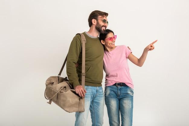 Pareja elegante aislada, mujer muy sonriente en camiseta rosa y hombre en sudadera con bolsa de viaje, vestido con jeans, gafas de sol, divirtiéndose juntos, señalando con el dedo