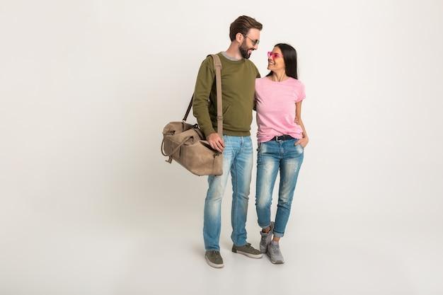 Pareja elegante aislada, mujer muy sonriente en camiseta rosa y hombre en sudadera con bolsa de viaje, vestido con jeans, gafas de sol, divirtiéndose juntos