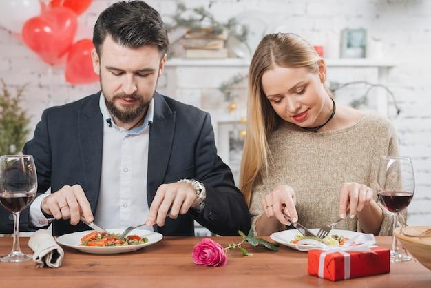 Pareja elegante comiendo en cita romántica