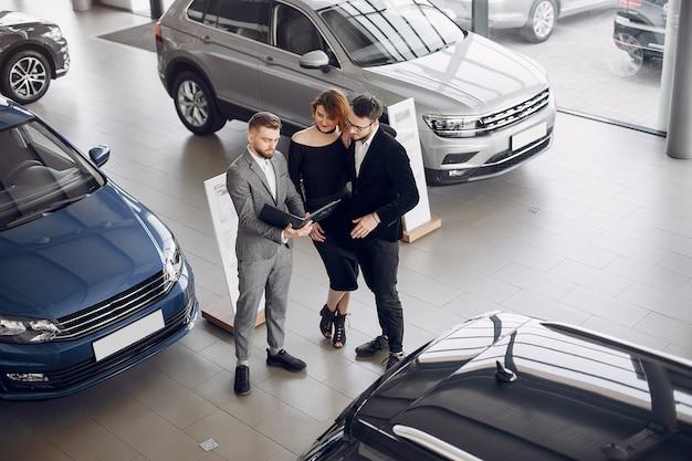 Pareja elegante y elegante en un salón de autos.