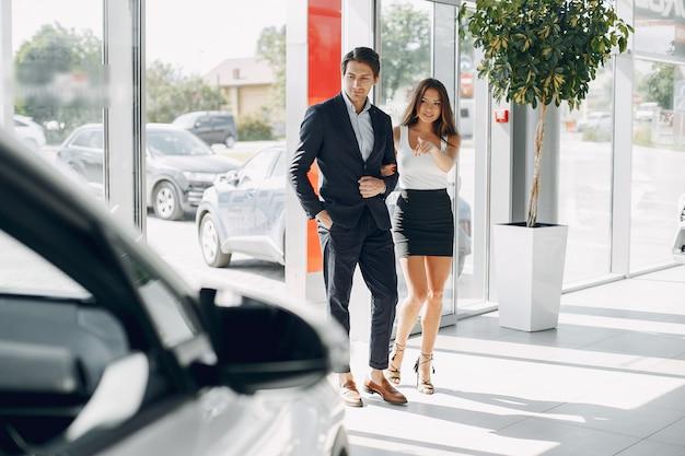 Pareja elegante y elegante en un salón de autos