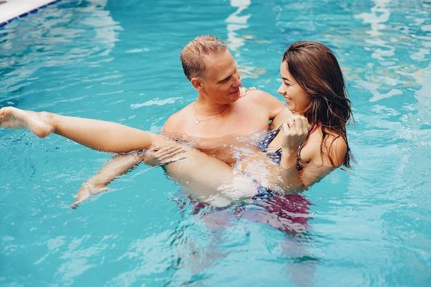 Pareja elegante nadar en la piscina