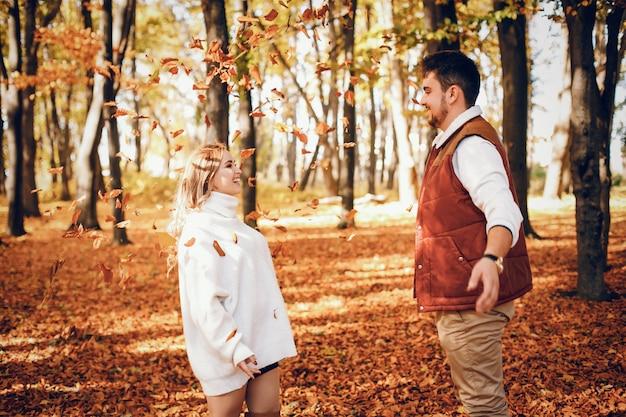 Pareja elegante en un parque soleado de otoño