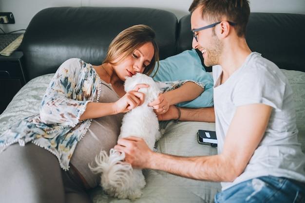 Pareja embarazada acostada en la cama relajante con cachorro